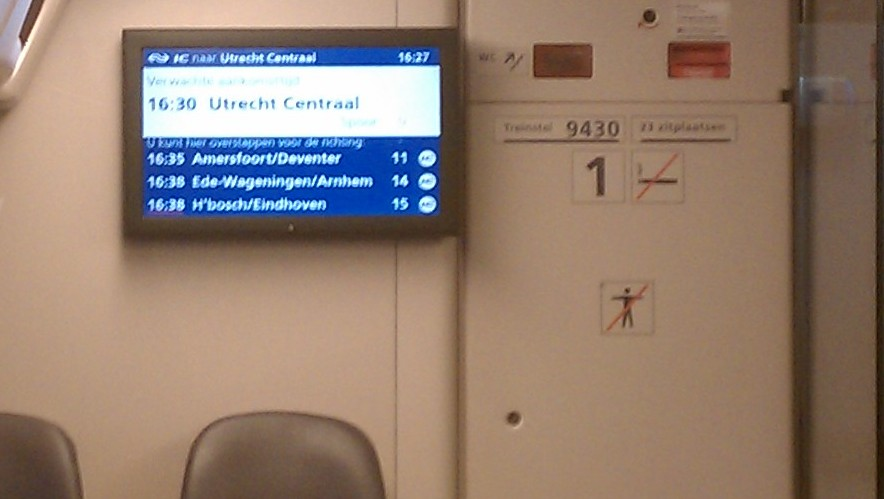 Blurry photo of info screen inside an NS InterCity train, with arrival and connection information. Photo by the author.