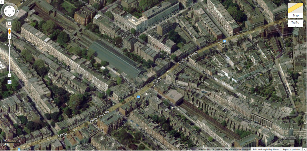 Aerial of Earl's Court Station. Note the railway in the open cut and the station buidlings above the tracks, presenting an unbroken street wall along Earl's Court Road. Image from Google Maps.
